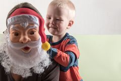 A happy child is holding a Santa Claus mask and an empty banner. Greeting card with Christmas. The concept of Christmas holidays.  Royalty Free Stock Photos