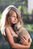Happy child holding a small dog. Happy child holding a small pugs puppy Royalty Free Stock Images