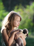 Happy child holding a small dog. Happy child holding a small pugs puppy Royalty Free Stock Photos