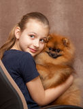Happy child holding a small dog. In studio Royalty Free Stock Photos