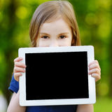 Happy child holding tablet PC outdoors Stock Photos