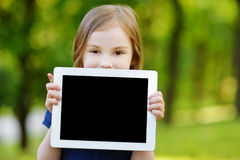 Happy child holding tablet PC outdoors Stock Photography