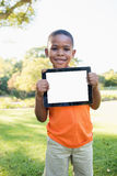 Happy child holding tablet pc while standing. In the park royalty free stock photos