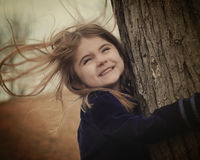 Happy Child Holding Tree in Wind. A little child is holding a tree with strong wind blowing in her hair. She is smiling and happy. Use for a weather or freedom Stock Photo