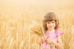 Happy child holding wheat ears Royalty Free Stock Photos