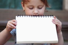 Happy child girl holding a white board with place for text. Happy child holding a white board with place for text royalty free stock images