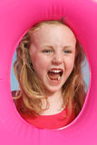 Happy child on holidays. Happy little girl shouting through a rubber float Royalty Free Stock Image