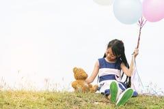 Happy Child hug teddy bear hold air balloon in green park playground. Teddy bear best friend for little kids cute girl. Autism