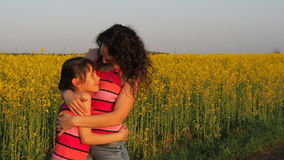 Happy child hugging mother in nature. A woman with a baby hugs in yellow flowers. Mom hugs her daughter. Emotions of the child stock footage