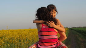 Happy child hugging mother in nature. A woman with a baby hugs in yellow flowers. Mom hugs her daughter. Emotions of the child. stock video