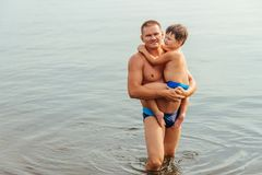 Happy child hugs his father standing in the lake. In the summer royalty free stock photos