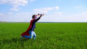 A happy child imagines a superhero and runs across the green grass, holding the plane. Joyful boy playing outdoors stock video footage