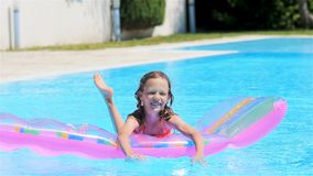 Adorable girl with inflatable mattress in outdoor swimming pool. Happy child with inflatable mattress having fun in swimming pool stock footage