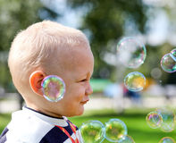 Happy child inflating soap-bubbles Royalty Free Stock Image