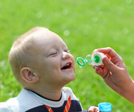 Happy child inflating soap bubbles Royalty Free Stock Photography