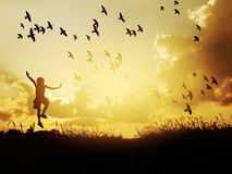 Happy child jumping with birds in sunset sky. Stock Photo
