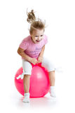 Happy child jumping on bouncing ball. Isolated on white Stock Image