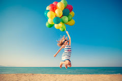 Happy child jumping with colorful balloons on sandy beach stock image