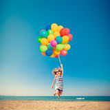 Happy child jumping with colorful balloons on sandy beach Royalty Free Stock Photography