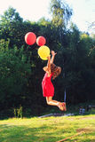 Happy child jumping with colorful toy balloons outdoors. Smiling royalty free stock photo