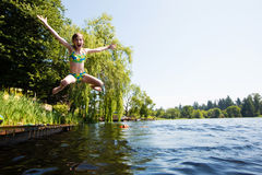 Happy child jumping in a lake Stock Image