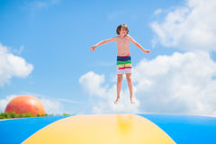Happy child jumping on a trampoline Stock Images