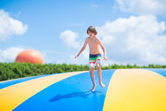 Happy child jumping on a trampoline Stock Photos