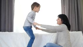 A happy child jumps on the bed holding his mother`s hands. Family: mom and son spend time playing together. stock video