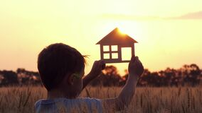 A happy child keeps a small house. The concept of construction, housing for a family. Construction business. Happy