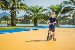 Happy child on kick scooter in on the basketball court. Kids learn to skate roller board. Little boy skating on sunny. Summer day. Outdoor activity for children royalty free stock images