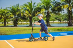 Happy child on kick scooter in on the basketball court. Kids learn to skate roller board. Little boy skating on sunny. Summer day. Outdoor activity for children royalty free stock photo