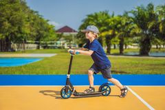 Happy child on kick scooter in on the basketball court. Kids learn to skate roller board. Little boy skating on sunny. Summer day. Outdoor activity for children royalty free stock photography
