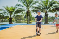 Happy child on kick scooter in on the basketball court. Kids learn to skate roller board. Little boy skating on sunny. Summer day. Outdoor activity for children stock image