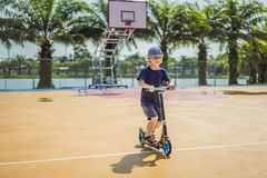 Happy child on kick scooter in on the basketball court. Kids learn to skate roller board. Little boy skating on sunny. Summer day. Outdoor activity for children stock images