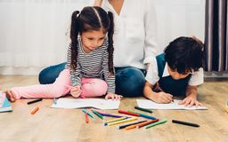Happy child kid boy and girl kindergarten drawing on peper teach stock photography