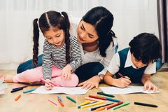 Happy child kid boy and girl son kindergarten drawing on peper teacher education with beautiful mother stock image