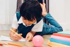 Happy child kid boy kindergarten drawing on peper teacher education. At interior room home stock photos