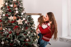Happy child kissing her mother near fir-tree. royalty free stock images