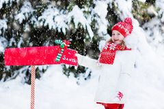 Child with letter to Santa at Christmas mail box in snow Royalty Free Stock Images