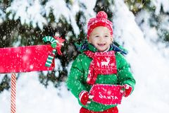 Child with letter to Santa at Christmas mail box in snow Stock Image