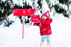 Child with letter to Santa at Christmas mail box in snow. Happy child in knitted reindeer hat and scarf holding letter to Santa with Christmas presents wish list Stock Images