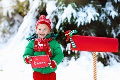 Child with letter to Santa at Christmas mail box in snow. Happy child in knitted reindeer hat and scarf holding letter to Santa with Christmas presents wish list Stock Photography