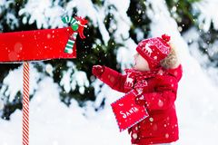 Child with letter to Santa at Christmas mail box in snow. Happy child in knitted reindeer hat and scarf holding letter to Santa with Christmas presents wish list Royalty Free Stock Images