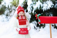 Child with letter to Santa at Christmas mail box in snow. Happy child in knitted reindeer hat and scarf holding letter to Santa with Christmas presents wish list Royalty Free Stock Photo