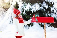 Child with letter to Santa at Christmas mail box in snow. Happy child in knitted reindeer hat and scarf holding letter to Santa with Christmas presents wish list Royalty Free Stock Photos