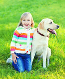 Happy child with labrador retriever dog on grass. In summer stock photos