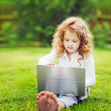 Happy child with laptop sitting on the grass. Stock Photos