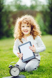 Happy child with laptop sitting on the grass. Royalty Free Stock Photos