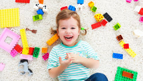 Happy child laughing and playing with toys constructor Stock Photo