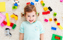 Happy child laughing and playing with toys constructor. Happy child girl laughing and playing with toys constructor Royalty Free Stock Images